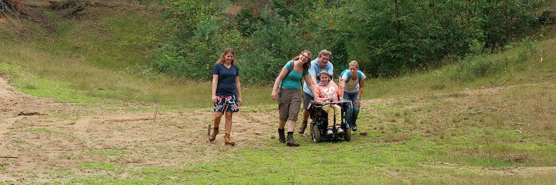 Mensen lopen een tocht samen met meisje in elektrische rolstoel