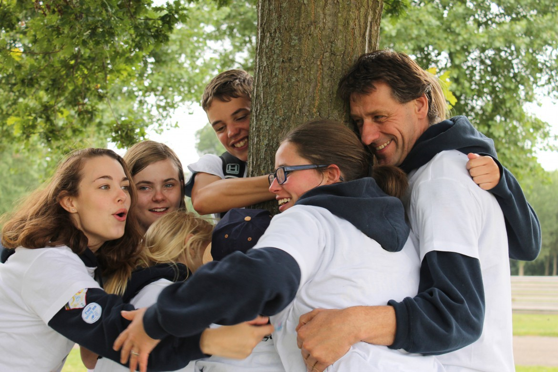 Mensen staan samen lachend bij een boom