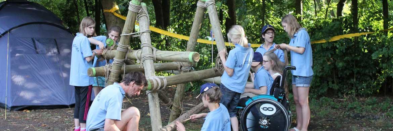Kinderen bouwen samen van hout en touw een bouwwerk