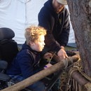 Kind in elektrische rolstoel maakt samen met begeleider een bouwwerk van touwen en hout op de regionale scoutingwedstrijden.